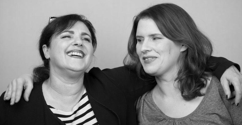 Zwei Frauen haben die Arme umeinander gelegt und lachen