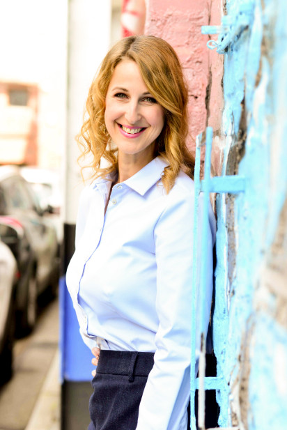 Lachende junge Frau steht an Wand gelehnt. Sie trägt eine hellblaue Bluse.