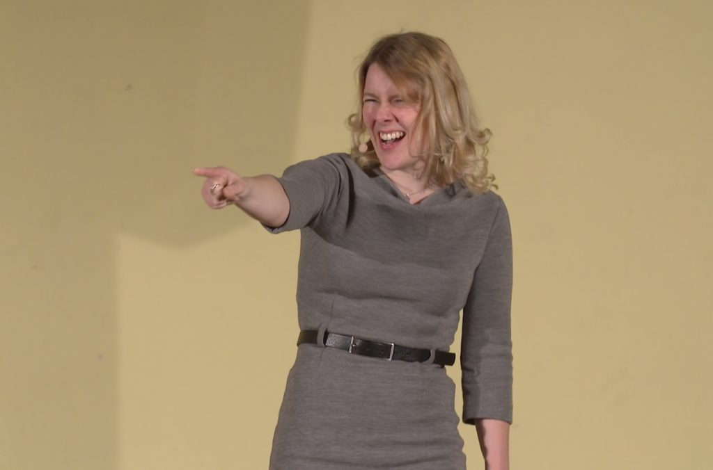 Tina Teucher, eine junge Moderatorin mit blonden Haaren und einem grauen Kleid von Alma und Lovis,  zeigt mit ausgestrecktem Arm motivierend an der Kamera vorbei.