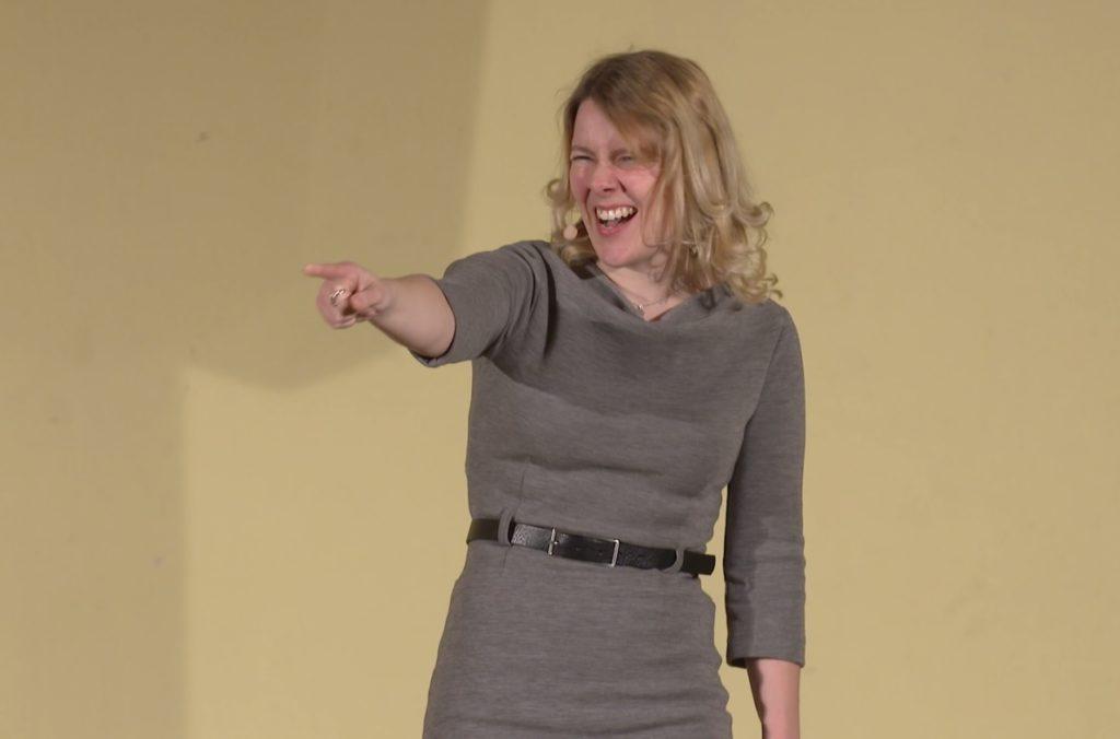 Tina Teucher, eine junge Moderatorin mit blonden Haaren und einem grauen Kleid, zeigt mit ausgestrecktem Arm motivierend an der Kamera vorbei.